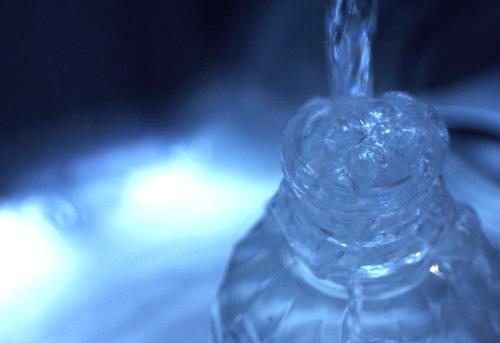 暗闇にあるペットボトルの水の画像