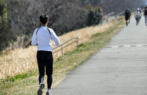 男性が白と黒の上下でランニングをする画像