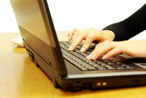 Female hands typing on laptop keyboard