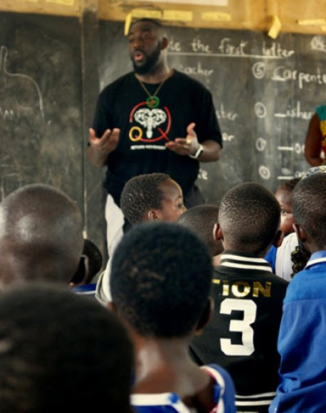 Isaac speaking with students at his former primary school in Ghana.