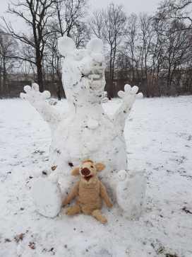 Wildschwein Wilma Wusel sitzt vor einer Wilma Wusel aus Schnee. Diese ist ein ganzes Stück größer als sie.