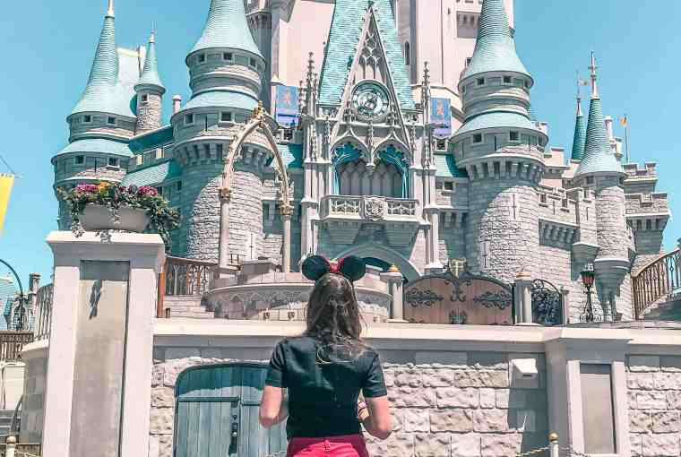 standing in front of cinderella castle at Walt Disney World in Orlando Florida