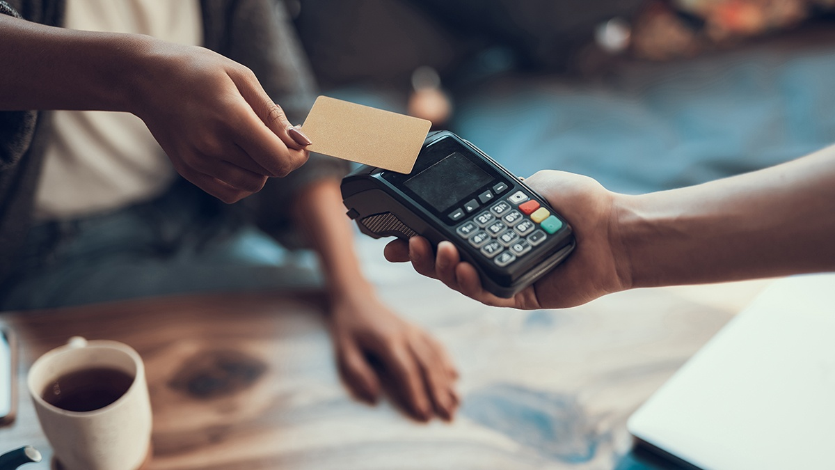 Someone scans a credit card on a payment machine