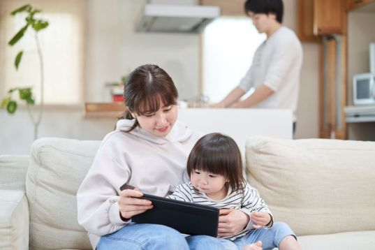 Dad cleaning kitchen while mom reads book with child on couch.