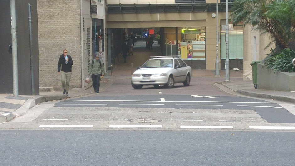 Driver turning into a garage across people