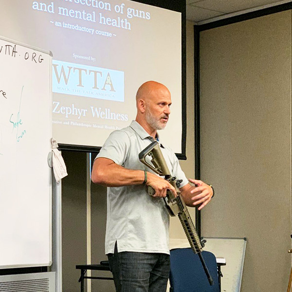An instructor with an assault rifle educates class of mental health professionals on its use
