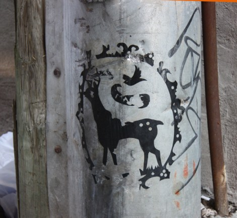 Sticker/paste-up by unknown artist in alley between St-Laurent and Clark