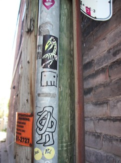 Stickers by various unknown artists in alley between St-Laurent and Clark