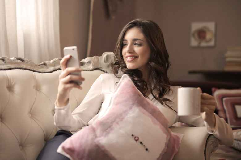 woman in white long sleeved shirt holding smartphone sitting on tufted sofa