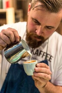 die-kunst-eines-perfekten-espresso-macchiato-zu-machen-beherrscht-der-barista-am-stand-der-kaffeeroesterei-wild_