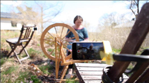 Josefin Waltin sitting outside by the spinning wheel. There are garden chairs around her with smartphones attached to them for filming.