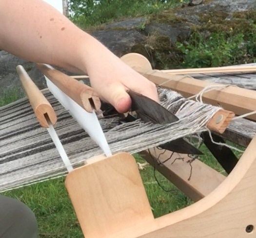 A hand cutting the warp of a rigid heddle loom with sheep shearers