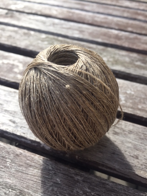 A hand wound ball of flax yarn.
