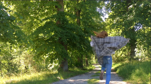 A person running with a plaid shawl behind her
