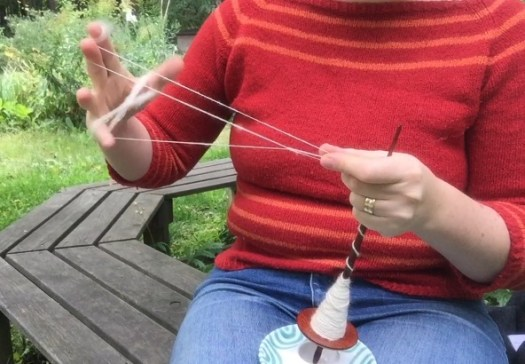 Close-up of a person chain-plying on a supported spindle