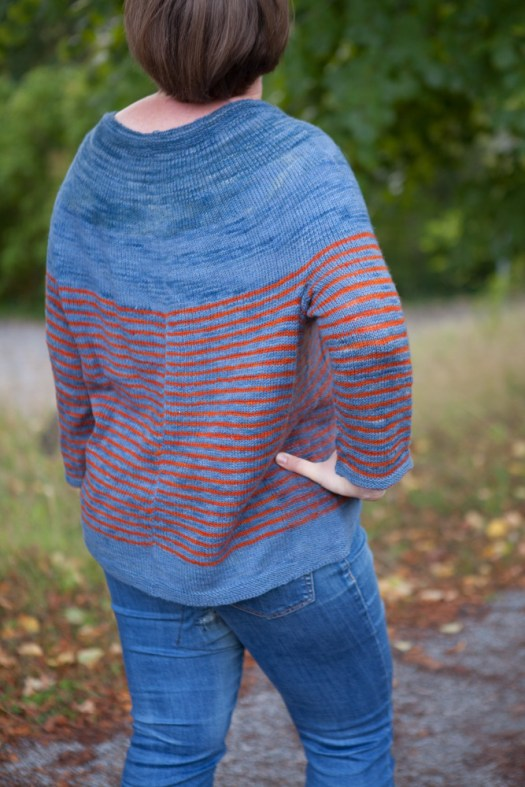 The back of a striped sweater in blue and orange