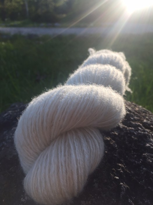 A skein of handspun white yarn in backlight.