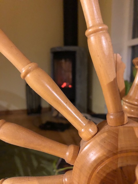 Close-up of a spinning wheel. A fireplace in the background.