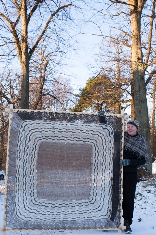 Josefin Waltin standing by a stretched Shetland hap.