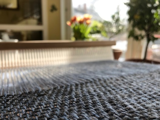 A rigid heddle weave with blue warp and dark grey weft