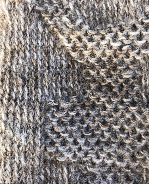 Close-up of a grey twined knitting mitten.