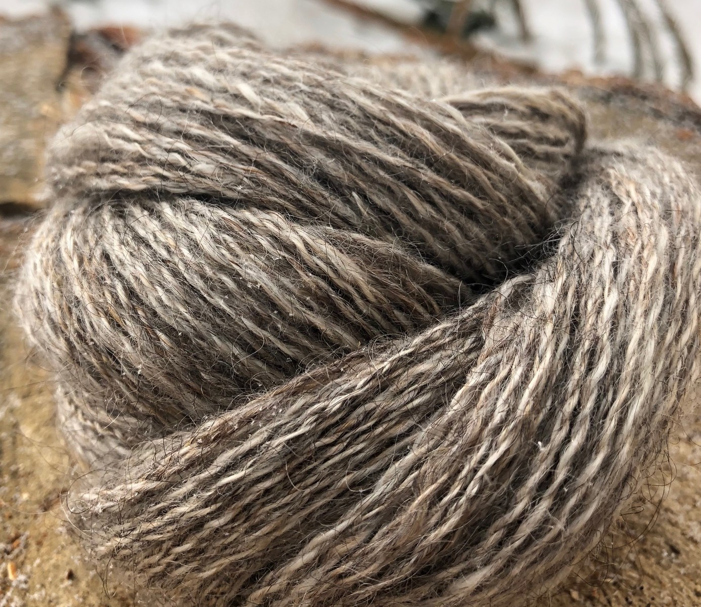 A skein of grey yarn rolled up into a bundle.