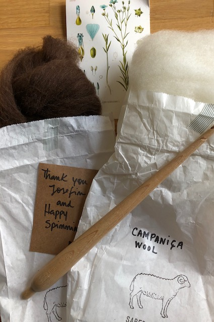 Two paper bags with wool and a spindle