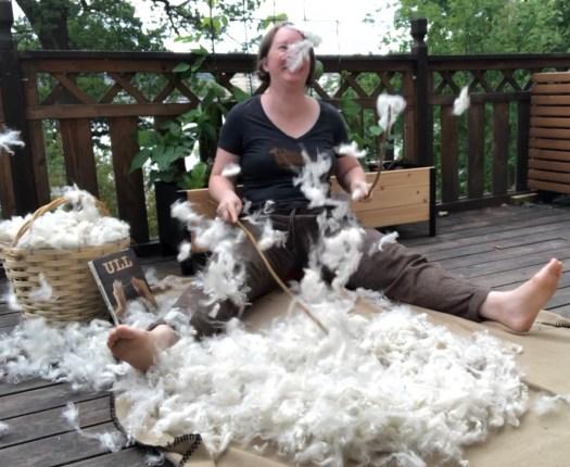 Josefin Waltin sitting on the ground, willowing wool