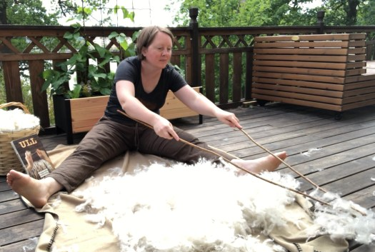 Josefin Waltin sitting on the ground with wool in front of her.