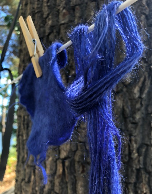 a bit of felted wool and a skein of yarn hanging on a washing line
