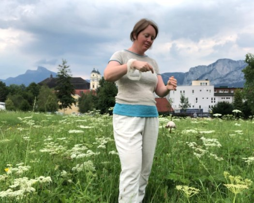 A woman spinning on a suspended spindle. She is standing in a meadow with mountains in the background