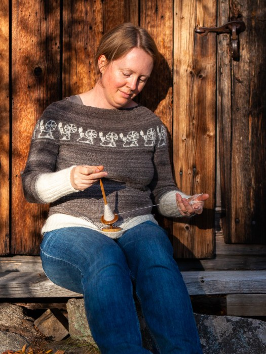 Josefin Waltin spinning on a supporter spindle and wearing a sweater with spinning wheels