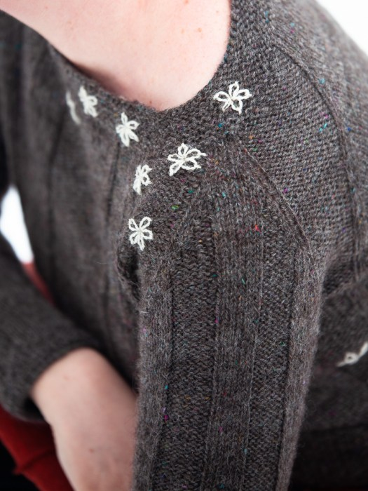 Close-up of a dark- grey knitted sweater with embroidered flowers.