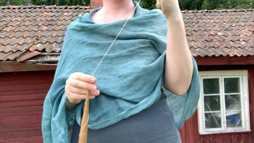 I spin by rolling my forefinger against the spindle shaft, supporting it with my thumb. My third and fourth fingers are balancing the spindle between them.