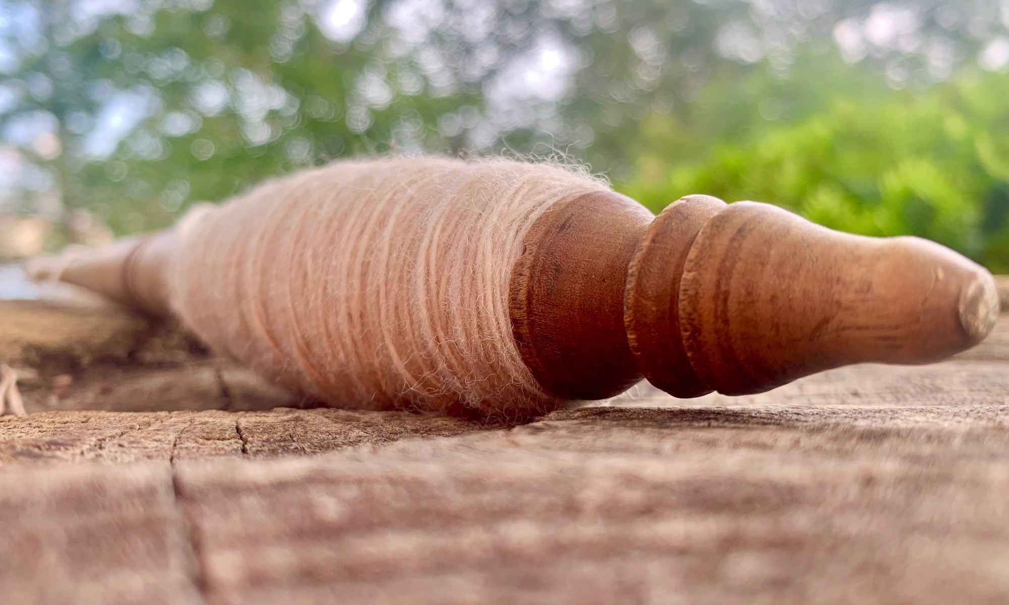 Close-up of an antique spindle with yarn wound onto it.