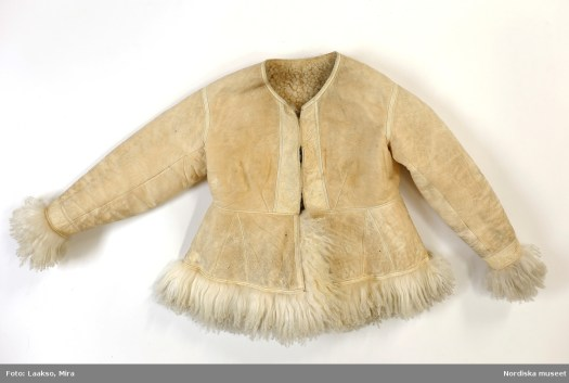 An old leather jacket with fur edgings in bottom and front hem and cuffs.