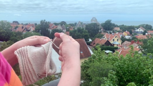 Close-up of a person knitting with two strands of yarn. A city in the background.