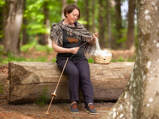 A woman sitting on a tree trunk and spinning on a ground-supported spindle. A basket of carded wool on the trunk beside her. She is wearing a T-shirt with a sheep on it and a woven plaid shawl.