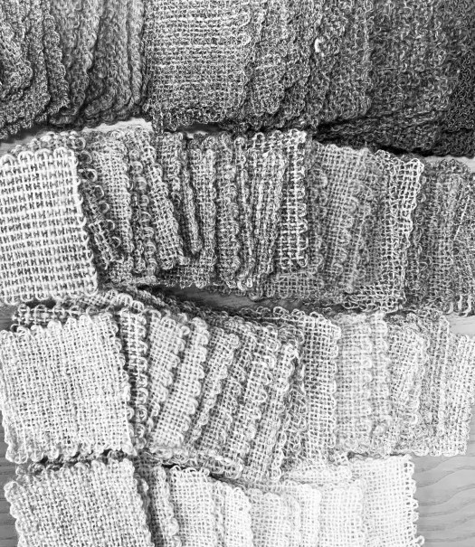 Lots of woven squares of the same size but in different shades of grey. The squares are arranged in a gradient from light to dark.
