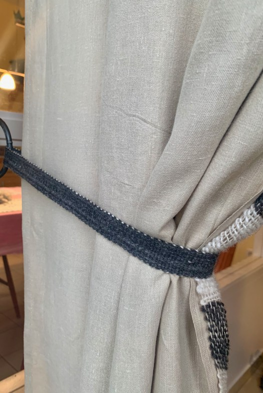 A linen sheet curtain tied back with a woven band.
