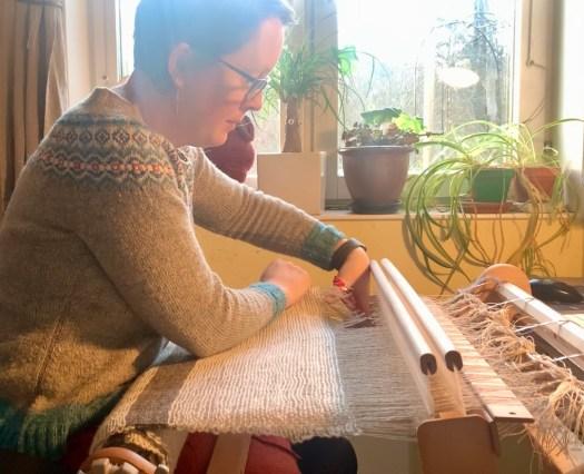 A woman cutting a warp.