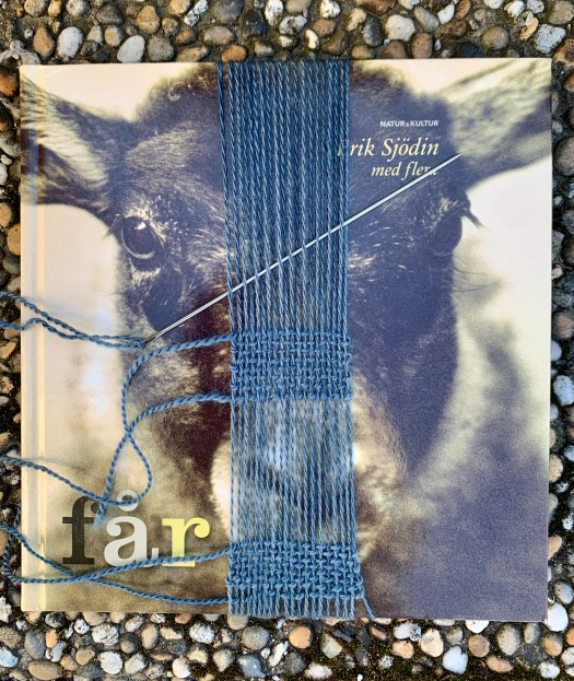 A weaving sample over a book. A sheep's head on the cover of the book.