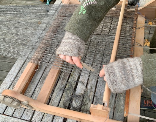 Close-up of a person pulling warp yarn through the slots of a rigid heddle. The person is wearing half-mitts.