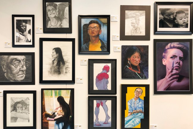 A wall full of framed portraits from the 2019 Scholastic Art Awards.