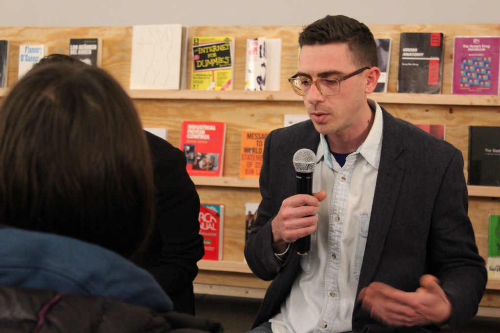 The artist speaks into a microphone surrounded by audience members. Behind the artist is a shelf containing books banned in U.S. prisons.