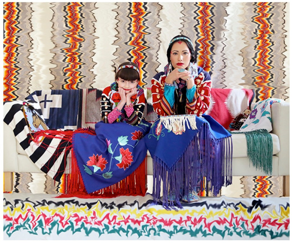 Wendy Red Star and her daughter are seated on a couch covered in blanket, quilts, and other textiles. A colorful, patterned background is behind them, with a different colorful, patterned background on the floor.