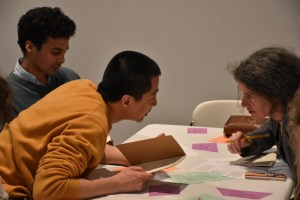 Artist Peng Wu leans across a table with colorful pieces of paper to whisper to another workshop participant.