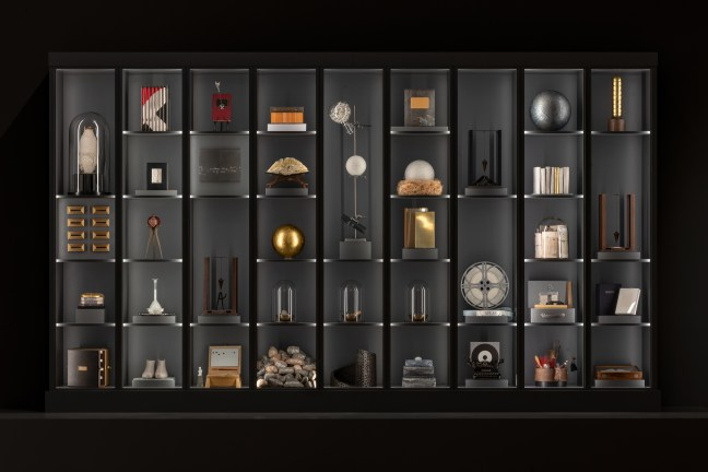 A very tall shelf with nine columns contains a number of different sculptural objects—a golden pendulum, a number of books, an old film machine. The objects are dramatically lit by light emanating from the frame.