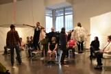 Dancers of all ages who wear hospital gowns with plastic gloves attatched are watched by a seated audience in the Target Studio Gallery at the Weisman.