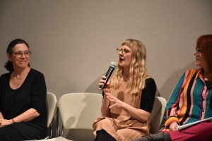 Artist Anna Marie Shogren, seated, holds a microphone during the panel of the Lifelong Choreographies performance.